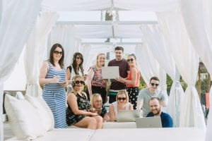 staff working from spain on laptops in the sun